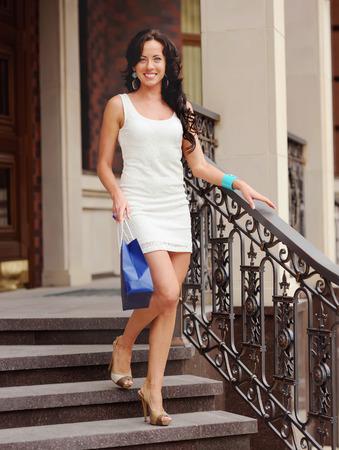 down stairs: Mujer hermosa en un vestido blanco con bolsa de compras caminando por las escaleras.