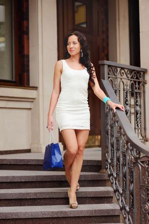 down the stairs: Mujer joven morena en vestido blanco con bolsa de compras caminando por las escaleras. Foto de archivo