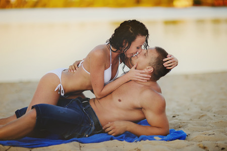 sexy topless women: Heterosexual Couple kissing on the beach Stock Photo
