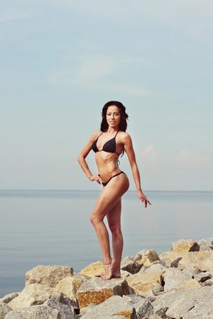 outdoor shot: outdoor shot of young woman in black bikini, perfect body