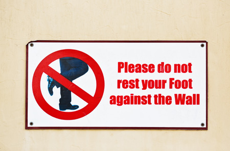 Please do not rest your feet on wall.  Street sign with restriction.