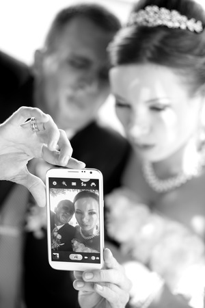 going crazy: Young just married couple taking pictures of themselves by smartphone, going crazy.