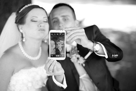 affectionate action: Wedding couple taking pictures of themselves by smartphone, going crazy.