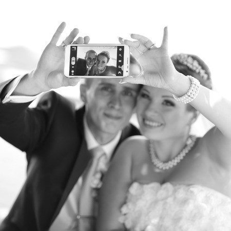 going crazy: Wedding couple taking pictures of themselves by smartphone, going crazy.