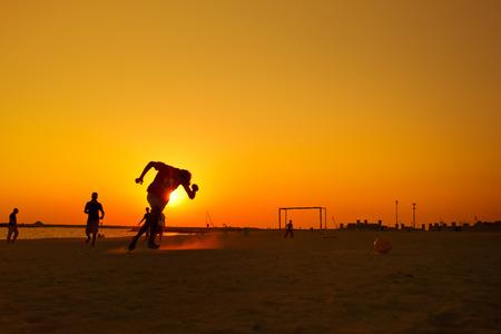 AFICIONADOS: Jugando al fútbol amateur en la playa durante la puesta de sol.