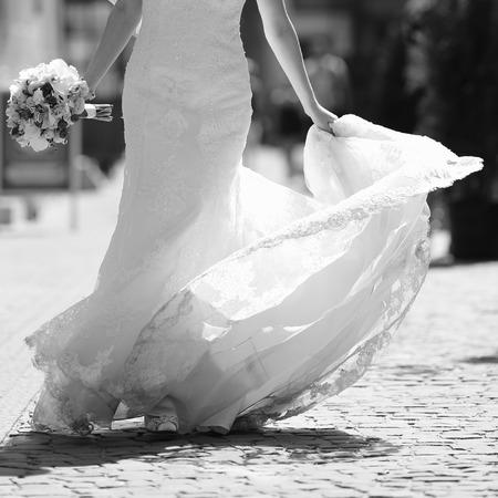 Stylish bride walking street, wedding fashion, black and white. Stock Photo