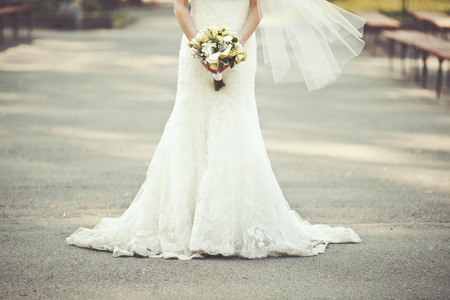 woman dress: wedding dress, bride holding a bouquet