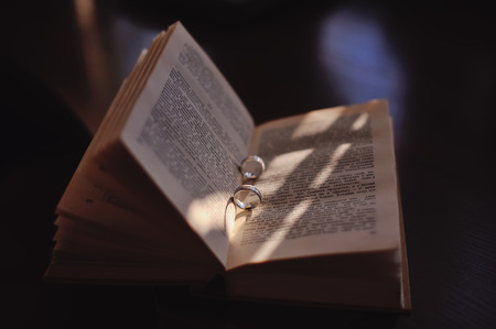descriptive colors: Wedding golden rings between pages of a russian book