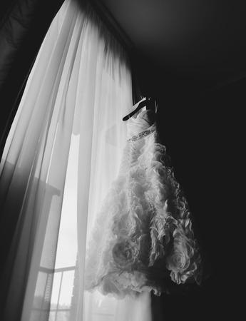 穏やかなウェディング ドレス。窓際。身に着けているための準備 写真素材