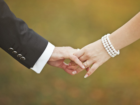 Marry me today and everyday. Newlywed couple holding hands, wedding picture. Stock Photo