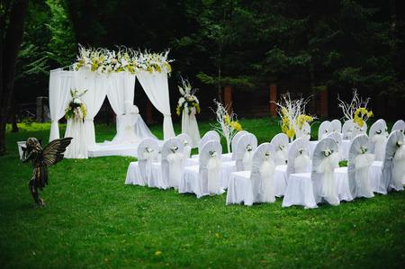 huwelijksceremonie in het bos, stoelen versierd met strikjes Stockfoto