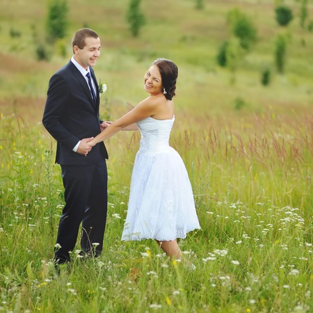 matrimony: Young groom and bride at field. Bonds of matrimony. Newlywed couple together. Stock Photo