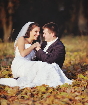Smiling young wedding couple in autumn forest. Bride and groom together.