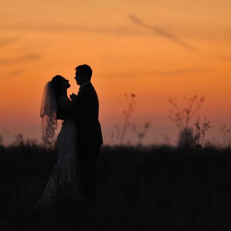 silueta masculina: Silueta de los pares de la boda en el campo. La novia y el novio juntos.