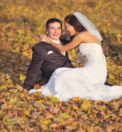wedlock: Young wedding couple sitting on yellow leaves. Newlywed couple together.