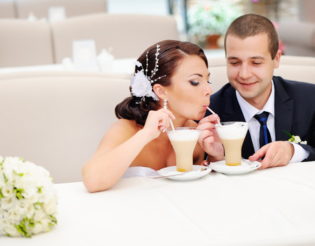 wed: Have a cappuccino honey. Newly wed couple  in cafe. Stock Photo