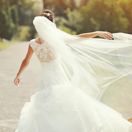 nude bride: happy bride spinning around with veil