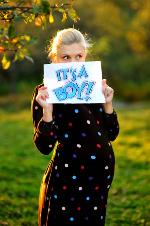 its a boy: Beautiful pregnant woman holding a sign which says its a boy!