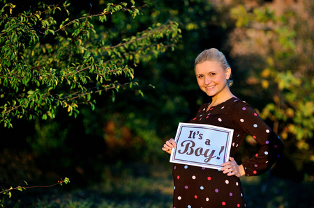 its a boy: pregnant woman  holding a sign which says its a boy! Stock Photo