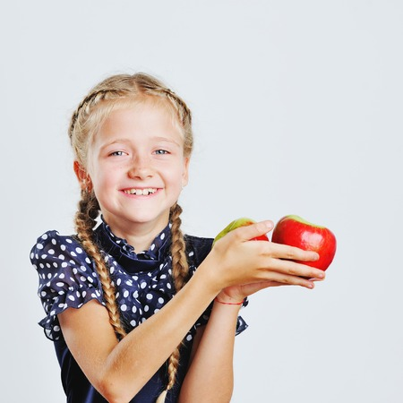 kinder garden: Happy little girl playing around with colorful apples