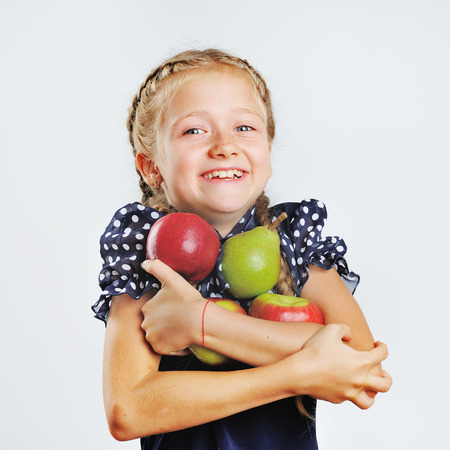 plaits: School girl with plaits  holding color apples. Stock Photo