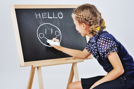 Smiling cute little girl grawing smilly faces on a blackboard