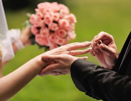 結婚して。新郎は彼の美しい妻の指に指輪をはめます。結婚式のカップルが一緒に。