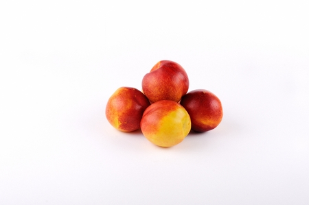 five objects: five peaches on a white background in a line
