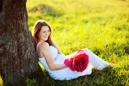 beautiful  pregnant woman with big red flower  posing in garden, toothy smile Stock Photo