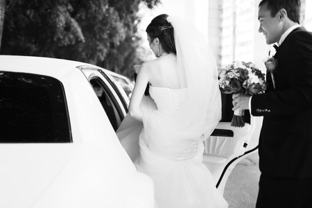 gets: Young bride gets into limo. Wedding couple.