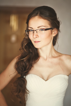 nuptial: Young caucasian bride wearing glasses at home waiting for groom.