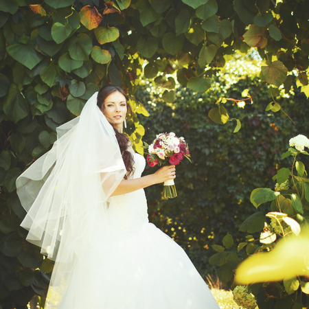 marriageable: Young caucasian bride in garden holding bouquet.