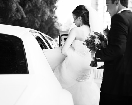 Young bride gets into limo. Wedding couple.