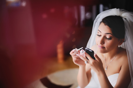 marriageable: Beautiful young bride is getting ready at home, having make up, using phone like a  mirror. Stock Photo
