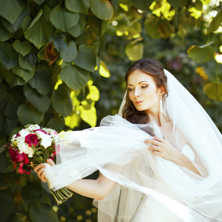 marriageable: Young caucasian bride playing with her veil in garden.
