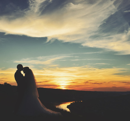 pareja de esposos: Joven recién casada pareja juntos en el fondo del atardecer.