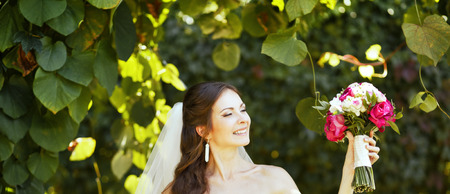 marriageable: Young caucasian bride posing with bouquet in garden. Stock Photo