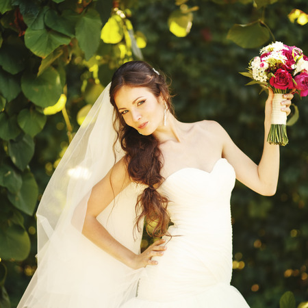 nuptial: Young caucasian bride posing with bouquet in garden. Stock Photo