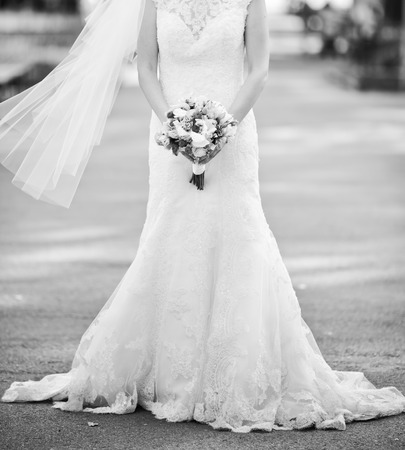 arm bouquet: beautiful wedding dress, bride holding a bouquet, black and white