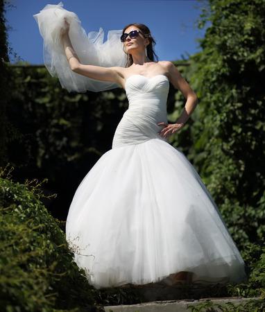 marriageable: Beautiful bride in sunglasses posing in garden.
