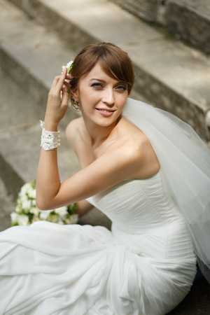 marriageable: Happy young bride laying on steps. Summertime picture.