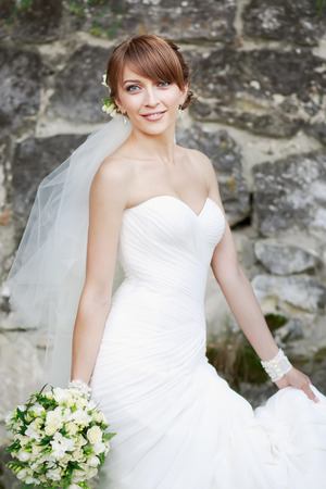 marriageable: Beautiful bride posing  against rock wall. Stock Photo