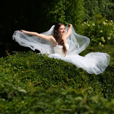 marriageable: Young caucasian bride playing with veil in garden.