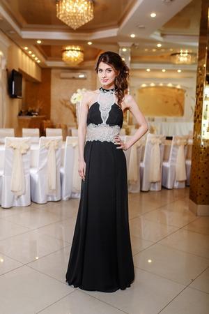 fresh graduate: Interior portrait of young brunette woman wearing blue prom dress.  Graduate student. Stock Photo