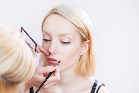artist model: Professional beautician artist applying makeup  on young model. Stock Photo
