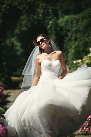 marriageable: She walks like a queen. Adorable young caucasian bride in garden, sunny summer day.