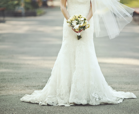 ślub: Piękna suknia ślubna, panna młoda trzyma bukiet