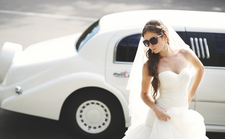 nuptial: Young bride against limo. Hot summer day. Wedding picture.