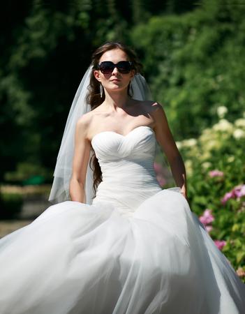 marriageable: Beautiful bride in sunglasses walking in garden. Stock Photo