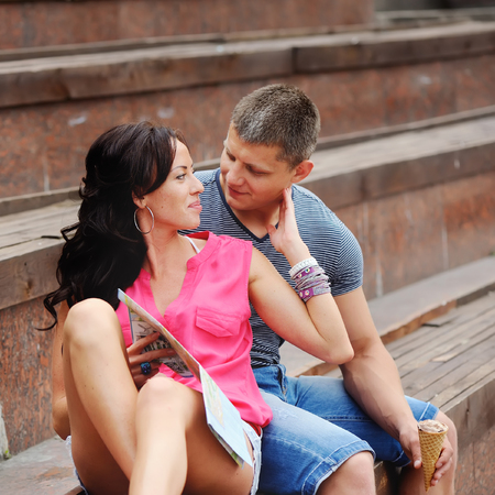 ice cream stand: Young couple of tourists sitting on steps